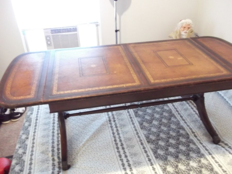 have a heritage henredon drop leaf coffee table with a leather top